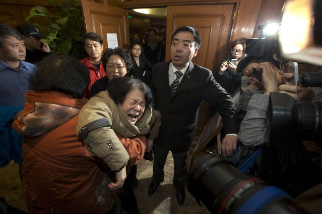 A relative of one of the Chinese passengers aboard the Malaysia Airlines, MH370 collapses in grief after being told of the latest news in Beijing, China, Monday, March 24, 2014. It was the grim news that families of the missing Malaysian Airlines flight had dreaded for weeks, and on Monday they heard it from Malaysia's prime minister: new analysis of satellite data indicates the missing plane crashed into a remote corner of the Indian Ocean. (Photo by Ng Han Guan/AP Photo)