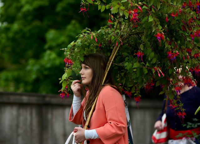 A woman carries a fuschia plant on the final day of the Royal Horticultural Society's Chelsea Flower Show in London, Britain, May 23, 2015. The show gardens traditionally sell off their plants at cheap prices to the lucky gardeners who can get their hands on tickets to the sold out event. (Photo by Dylan Martinez/Reuters)