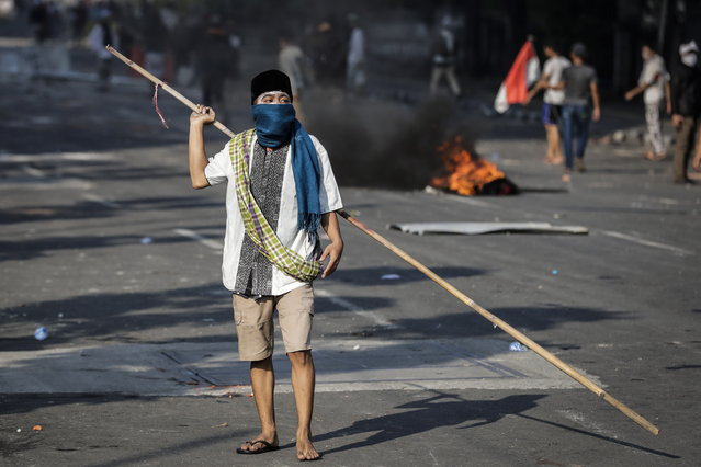 An Indonesian protester holds a bamboo stick during a clash with riot police officers following the announcement of the presidential election results outside Election Supervisory Board (Bawaslu) building in Jakarta, Indonesia, 22 May 2019. Incumbent Indonesian President, Joko Widodo was re-elected after winning the presidential election over his rival, retired General Prabowo Subianto, the election commission announced on 21 May 2019. (Photo by Mast Irham/EPA/EFE)