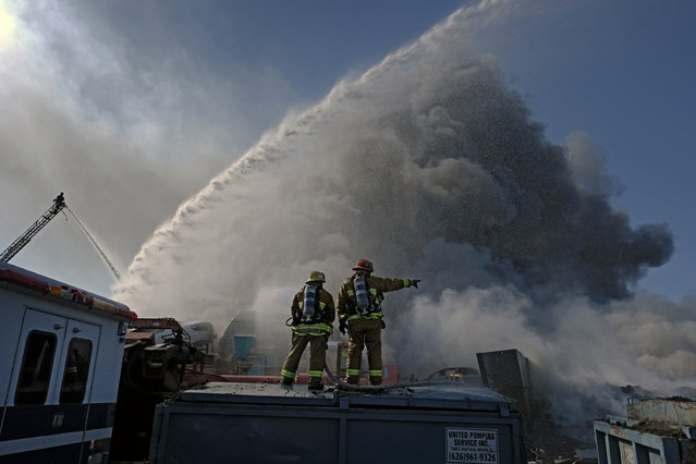 Firefighters work a fire at an auto wrecking yard in the Sun Valley section of Los Angeles in the San Fernando Valley as a huge plume of thick, black smoke rises over them on Sunday, April 17, 2016. The Fire Department is calling the fire a major emergency but no injuries have been reported and no buildings are threatened. (Photo by Richard Vogel/AP Photo)