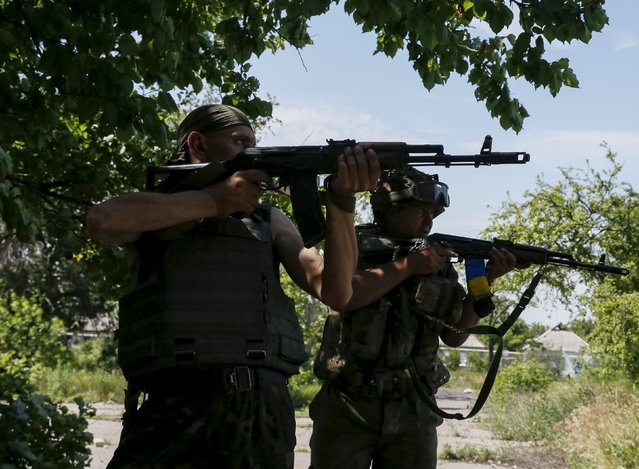 """Members of the Ukrainian armed forces patrol the area in the town of Maryinka, eastern Ukraine, June 5, 2015. Ukraine's president told his military on Thursday to prepare for a possible """"full-scale invasion"""" by Russia all along their joint border, a day after the worst fighting with Russian-backed separatists in months.  REUTERS/Gleb Garanich"""