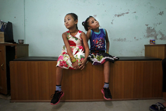 In this September 8, 2015 photo, best of friends Khendo Tamang, left, and Nirmala Pariyar, both 8, wait to be measured for a new prosthetic legs in Kathmandu, Nepal. (Photo by Niranjan Shrestha/AP Photo)