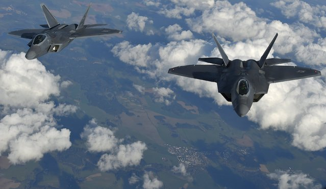 Two U.S. F-22 Raptor fighters fly over European airspace during a flight to Britain from Mihail Kogalniceanu air base in Romania April 25, 2016. (Photo by Toby Melville/Reuters)