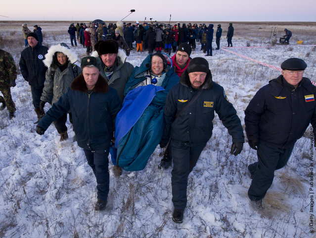 Expedition 29 Commander Mike Fossum smiles as he is carried in a chair to the medical tent just minutes after he and Expedition 29 Flight Engineers Sergei Volkov and Satoshi Furukawa landed