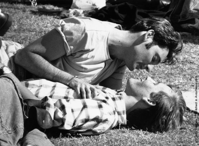 Two young men sharing a tender moment on the grass during a Gay Pride festival in London, 1996