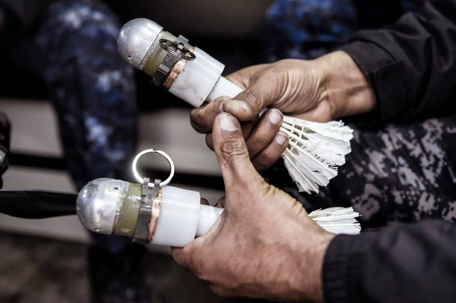 A member of the Iraqi forces carries two grenades carrying feathers, which are to be fired from a drone in the fight against Islamic State (IS) group jihadists in the northern Iraqi city of Mosul on March 14, 2017. IS have used small drones to drop explosives on advancing Iraqi forces since they launched the battle to retake the whole of Iraq's second city in October. But now, Iraqi forces have adopted the terrifying tactic, equipping their own remote-controlled devices with 40-mm grenades. (Photo by Aris Messinis/AFP Photo)