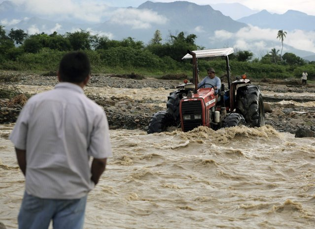 People who live in the countryside outside the town of Chiclayo, 770 kilometres north of Lima, use a tractor to cross the rising waters of the Zana River on March 19, 2017. (Photo by Julio Reaño/AFP Photo)