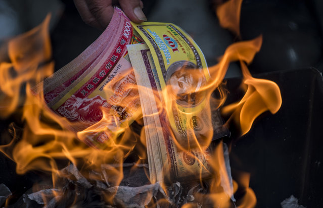 "A man burns ghost money to pay his respects to his ancestors in front of a gravestone during the annual ""Qingming"" festival, or Tomb Sweeping Day, at a public cemetery in Shanghai on April 4, 2017. During Qingming, Chinese traditionally tend the graves of their departed loved ones and often burn paper money, model houses, cars, mobile phones and other goods as offerings to honour them and keep them comfortable in the afterlife. (Photo by Johannes Eisele/AFP Photo)"