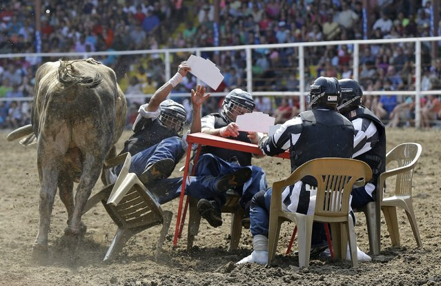 A bull rams inmates seated at a card table in the Convict Poker event at the Angola Prison Rodeo in Angola, La., Saturday, April 26, 2014. Those competing in the rodeo have to pass a physical to be deemed strong and healthy enough, and thousands of others work year-round making arts and crafts to sell at the event, according to the prison's athletic director. (Photo by Gerald Herbert/AP Photo)