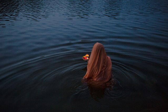 "An Indian women offers early-morning prayers or a ""puja"" at a ghat early in the morning on the banks of the Betawa River in Orchha in the state of Madhya Pradesh on July 5, 2015. (Photo by Rebecca Conway/AFP Photo)"