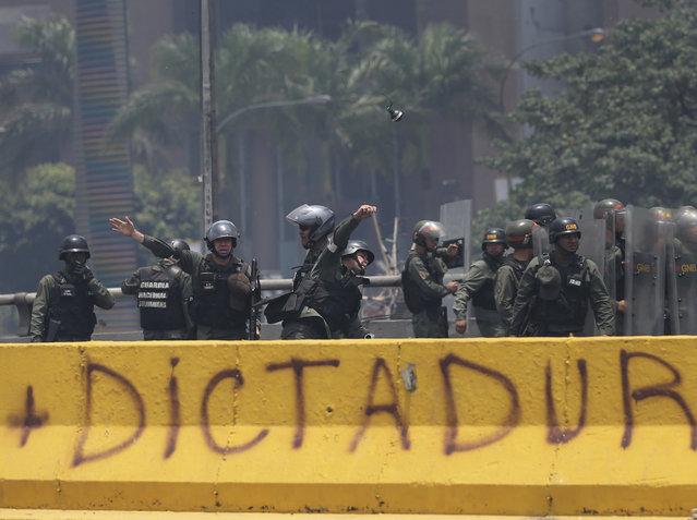A Venezuelan Bolivarian National Guard officer throws a tear gas grenade towards demonstrators during a protest in Caracas, Venezuela, Monday, April 10, 2017. (Photo by Fernando Llano/AP Photo)