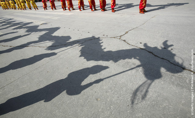 Folk artists performing a dragon dance cast a shadow on the ground during the Lantern Festival