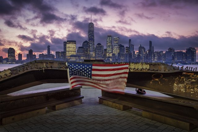 A U.S. flag hanging from a steel girder, damaged in the September 11, 2001 attacks on the World Trade Center, blows in the breeze at a memorial in Jersey City, N.J., Sept. 11, 2019 as the sun rises behind One World Trade Center building and the re-developed area where the Twin Towers of World Trade Center once stood in New York City on the 18th anniversary of the attacks. (Photo by J. David Ake/AP Photo)