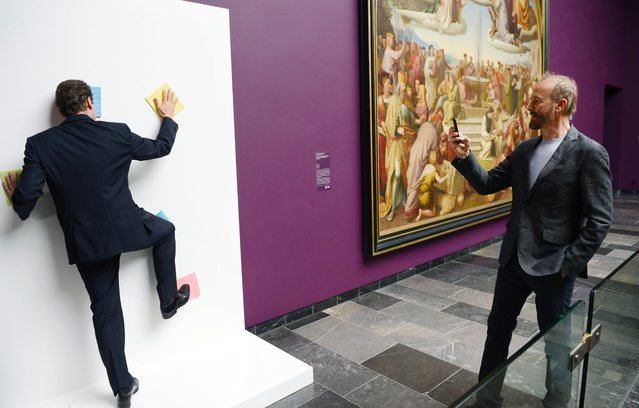 """Staedel director Max Hollein demonstrates Erwin Wurm's participation sculpture """"Theory of Painting"""" as he photographs Hollein in the Staedel Museum, in Frankfurt am Main, Germany, 06 May 2014. The series """"Wurm: One Minute Sculptures"""" include painted or written instructions tell the person what they have to do and where for 60 seconds. The exhibition runs from 07 May to 13 July. (Photo by Arne Dedert/EPA)"""