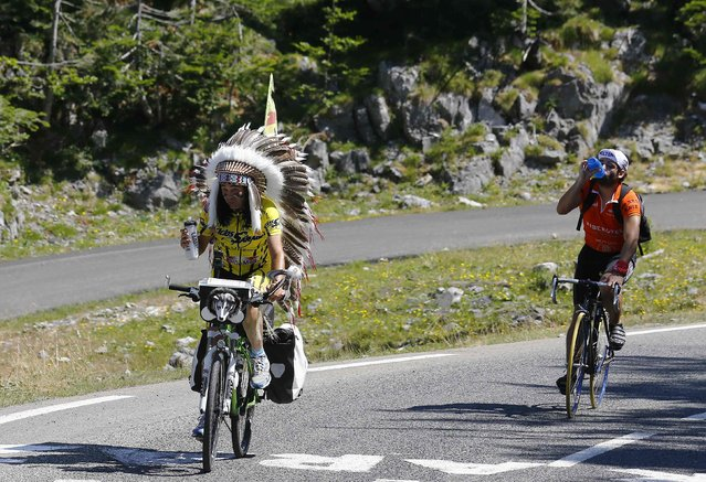 A supporter of Movistar rider Alejandro Valverde of Spain dressed as an American Indian climbs on his bicycle before the 167-km (103.7 miles) 10th stage of the 102nd Tour de France cycling race from Tarbes to La Pierre-Saint -Martin, France, July 14, 2015. (Photo by Stefano Rellandini/Reuters)