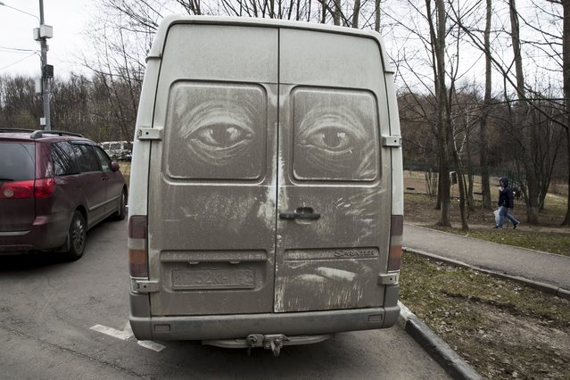 In this photo taken on Saturday, April 22, 2017, a face with reptilian eyes is drawn on the back of a dirty vehicle by artist Nikita Golubev in Moscow, Russia. (Photo by Pavel Golovkin/AP Photo)