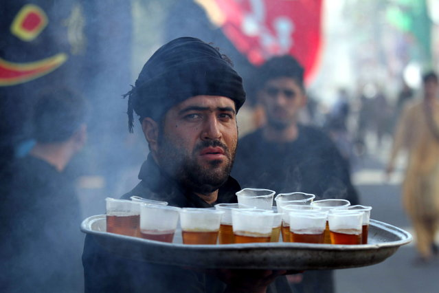 An Afghan Shiite Muslim serves drinks to mourners at an Ashura mourning procession during the Islamic sacred month of Muharram in Herat, Afghanistan, 10 September 2019. Shiite Muslims are observing the holy month of Muharram, the climax of which is the Ashura festival that commemorates the martyrdom of Imam Hussein, a grandson of the Prophet Mohammed, in the Iraqi city of Karbala in the seventh century. (Photo by Jalil Rezayee/EPA/EFE)