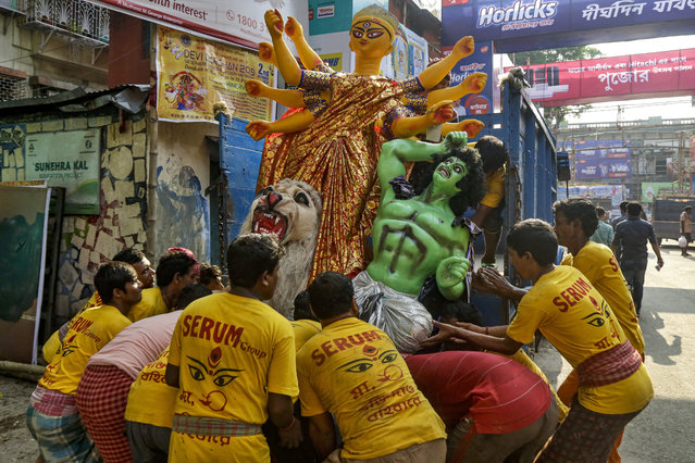 Indian laborers lift an idol of Hindu goddess Durga on a truck ahead of Hindu festival Durga Puja in Kolkata, India, Wednesday, October 2, 2019. The festival is scheduled to run from Oct. 5 to Oct. 8. (Photo by Bikas Das/AP Photo)