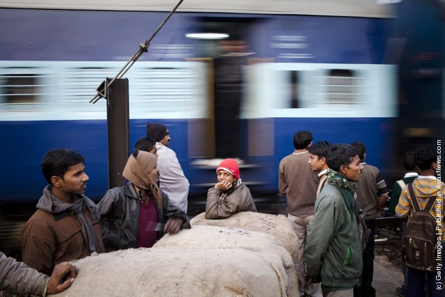 Workers wait to cross tracks as a train to passes nearby to the Nizamuddin Railway Station in New Delhi, India