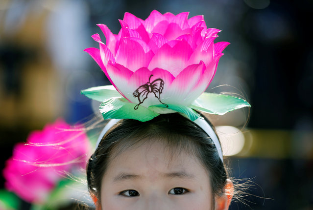 A child wearing a lantern headband rests before a Lotus Lantern parade in celebration of the upcoming birthday of Buddha in Seoul, South Korea April 29, 2017. (Photo by Kim Hong-Ji/Reuters)