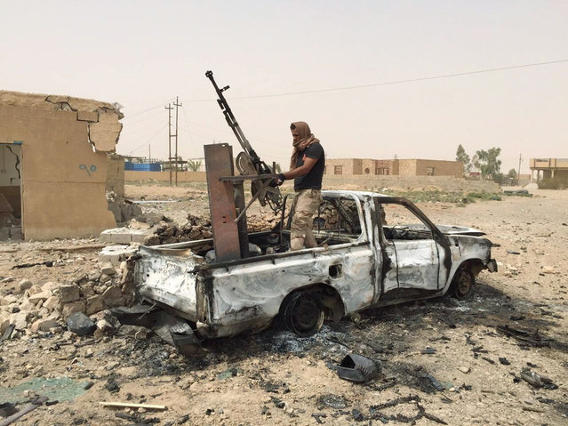 A militiaman allied with the Iraqi security forces dismantles a weapon from a destroyed vehicle belonging to the Islamic State group following a U.S.-led coalition airstrike against IS positions in southern Ramadi, Anbar province, Iraq, Monday, July 20, 2015. Iraqi security officials said that militants from the Islamic State group blew up a sports stadium near the militant-held city of Ramadi. (Photo by AP Photo)