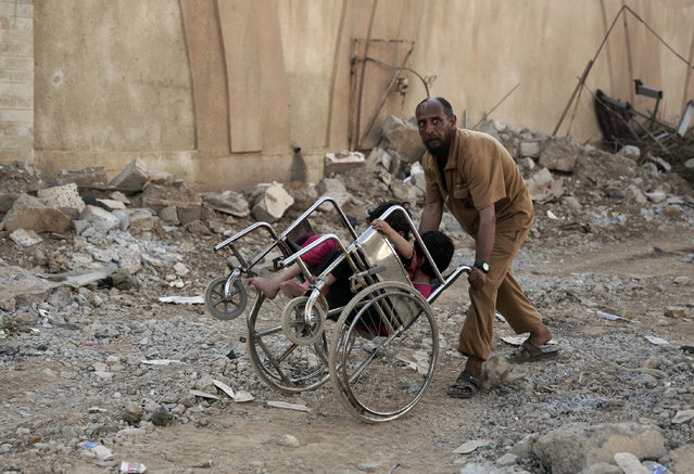 A man pushes two children in a wheelchair as they flee heavy fighting between Islamic State militants and Iraqi special forces in Mosul, Iraq, Wednesday, May 10, 2017. (Photo by Maya Alleruzzo/AP Photo)