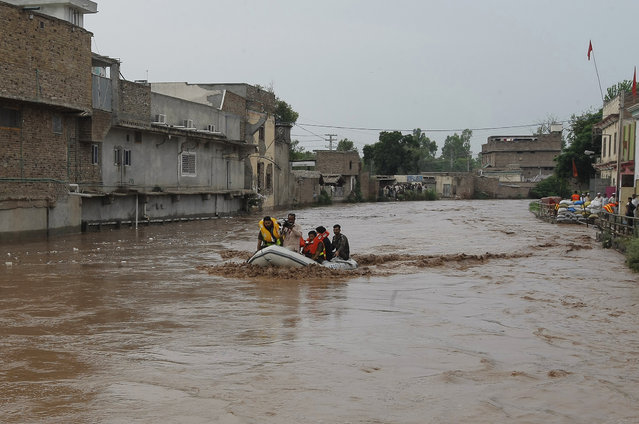 Pakistani volunteers evacuate marooned people after heavy rains in a suburb of Peshawar, Pakistan, Thursday, July 23, 2015. (Photo by Mohammad Sajjad/AP Photo)
