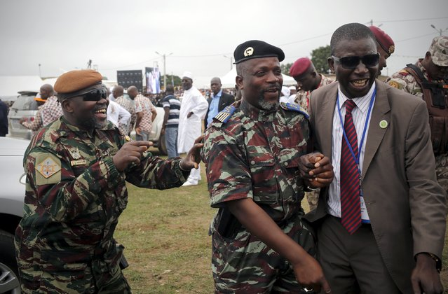 Morou Outtara (L) and Kone Zakaria (C), former warlords of Ivorian rebelion who now all named as lieutenant-colonels by Ivory Coast's President Alassane Ouattara, joke during the president's visit in the city of Mankono, in northwestern Ivory Coast July 24, 2015. (Photo by Luc Gnago/Reuters)