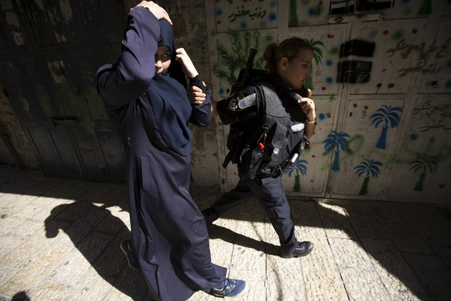 An Israeli police officer detains a Palestinian protester in Jerusalem's Old City, on Tisha B'Av July 26, 2015. (Photo by Amir Cohen/Reuters)