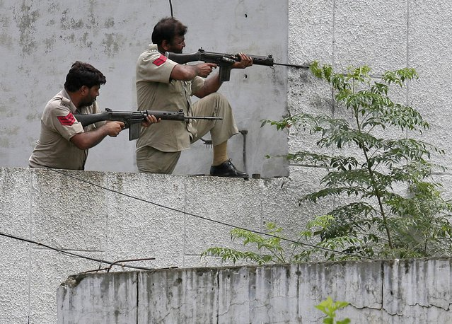 Indian policemen take their positions next to a police station during a gunfight at Dinanagar town in Gurdaspur district of Punjab, India, July 27, 2015. (Photo by Munish Sharma/Reuters)