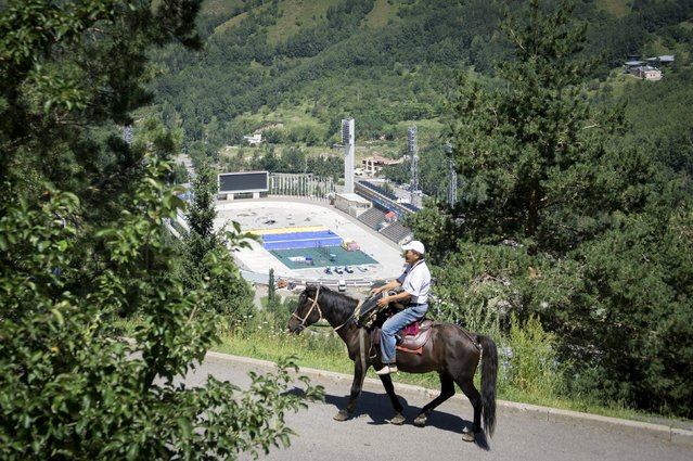 A man rides a horse near the Medeu skating oval in Almaty, Kazakhstan, July 26, 2015. (Photo by Shamil Zhumatov/Reuters)