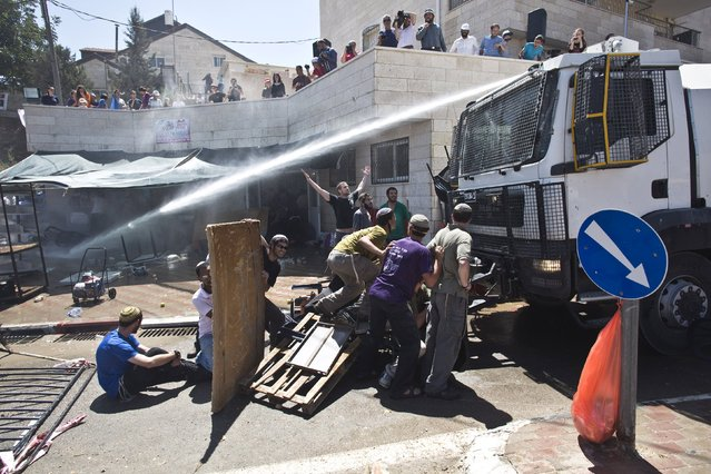 Israeli forces spray water on Jewish settlers protesting the demolition of two partially-built dwellings in the West Bank Jewish settlement of Beit El near Ramallah July 29, 2015. (Photo by Emil Salman/Reuters)