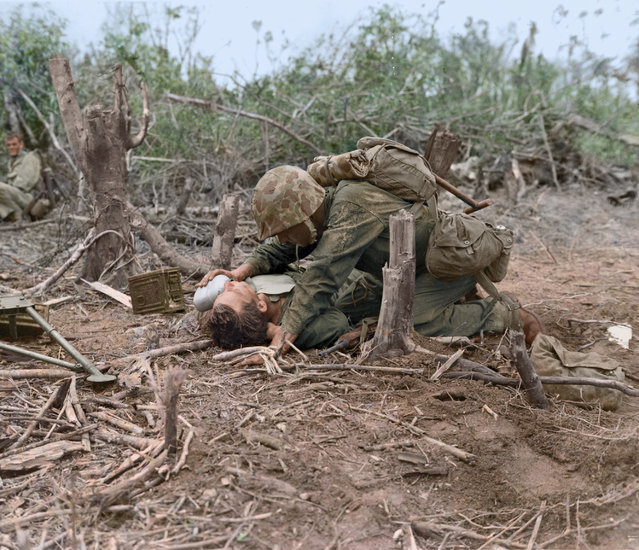 A wounded Marine, while he waits for the stretcher bearers to come for him, is given a drink of water from the canteen of a buddy while the Marines fight the enemy in rough country. (Photo by Jared Enos/Mediadrumworld.com)