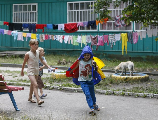 Children play in the compound of a health and rest centre which serves as a temporary accommodation for refugees from eastern regions of the country, with a dog seen in the background, in the town of Korostyshiv, Zhytomyr region, Ukraine, July 30, 2015. (Photo by Valentyn Ogirenko/Reuters)