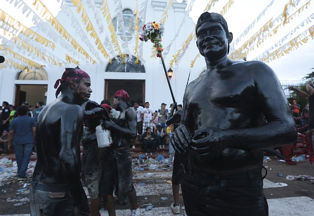 Devotees covered in motor oil take part in celebrations honoring the patron saint of Managua, Santo Domingo de Guzman, in Managua, Nicaragua August 1, 2015. (Photo by Oswaldo Rivas/Reuters)