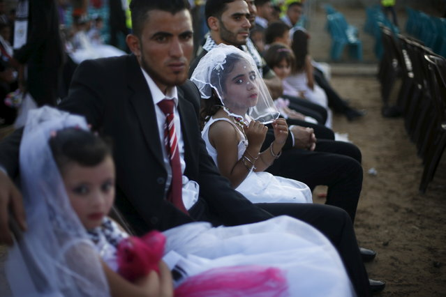 Girls accompany grooms as they sit separate from the brides during a mass wedding for 150 couples in Beit Lahiya town in the northern Gaza Strip July 20, 2015. The wedding was funded by al-Basheer Society for Relief and Development. (Photo by Suhaib Salem/Reuters)