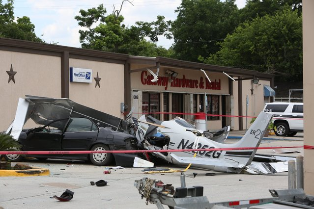 A small plane that crashed into a car in a parking lot near a Houston airport is roped off on Thursday, June 9, 2016. The  aircraft had been trying to land at Hobby Airport, in the southeastern part of the city,  when it crashed less than a mile northwest of the airport, said Lynn Lunsford, a spokesman for the Federal Aviation Administration. (Photo by Steve Gonzales/Houston Chronicle via AP Photo)