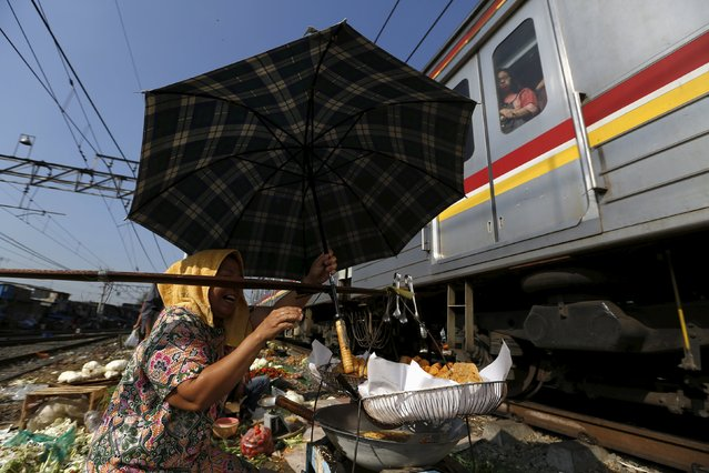 A woman holds her umbrella while selling food as a train passes through a vegetable market located on train tracks near Duri train station in Jakarta, Indonesia August 3, 2015. (Photo by Reuters/Beawiharta)