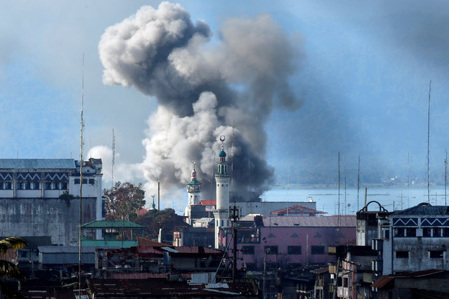 An explosion is seen after a Philippines army aircraft released a bomb during an airstrike as government troops continue their assault against insurgents from the Maute group in Marawi city June 27, 2017. (Photo by Jorge Silva/Reuters)