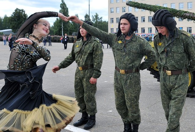 A Belarus cadet holds the hand of a woman while she dances during a graduation ceremony on June 28, 2014 at the Military Academy, outside Minsk. (Photo by Viktor Drachev/AFP Photo)