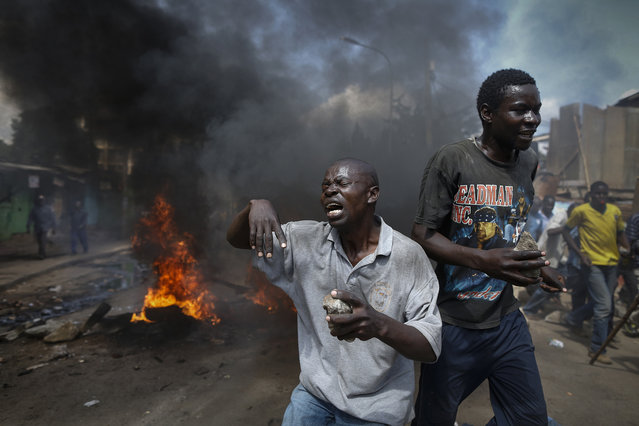 Opposition supporters react in front of a burning barricade they set up in the Kibera slum of Nairobi, Kenya, as they protest against an MP Moses Kuria of the ruling Jubilee coalition who allegedly called for the assassination of opposition leader Raila Odinga, June 14, 2016. (Photo by Dai Kurokawa/EPA)