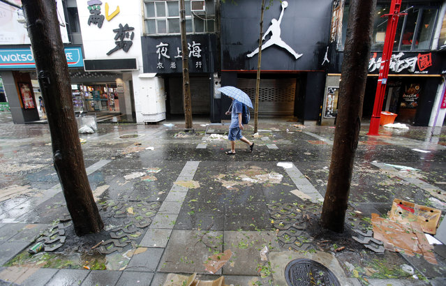 A man passes through debris from Typhoon Soudelor in Taipei, Taiwan, Saturday, August 8, 2015. (Photo by Wally Santana/AP Photo)