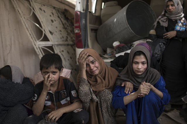 Fleeing Iraqi civilians sit inside a house as they wait to be taken out of the Old City during fighting between Iraqi forces and Islamic State militants in Mosul, Iraq, Saturday, July 8, 2017. (Photo by Felipe Dana/AP Photo)