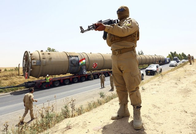 A member of the Kurdish security forces takes up position with his weapon as he guards a section of an oil refinery, which is being brought on a truck to Kalak refinery in the outskirts of Arbil, in Iraq's Kurdistan region, July 14, 2014. (Photo by Reuters/Stringer)
