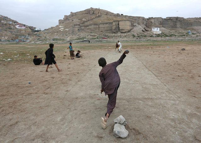 Afghan children play cricket on the outskirts of Kabul, Afghanistan, Monday, August 3, 2015. (Photo by Rahmat Gul/AP Photo)