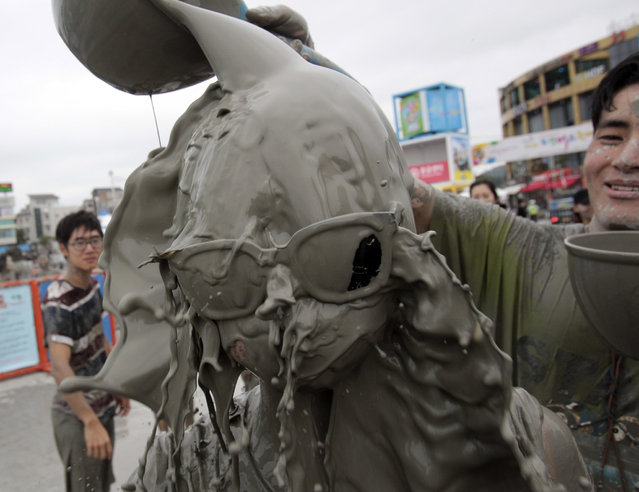A man pours mud water on the head of his girl friend during the Boryeong Mud Festival at Daecheon Beach in Boryeong, South Korea, Friday, July 18, 2014. The annual mud festival features mud wrestling and mud sliding. (Photo by Ahn Young-joon/AP Photo)