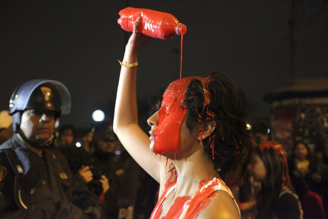 A pro-abortion activist pours red paint on her head during a march towards the Congress to support a proposal to change Peruvian abortion laws in Lima, August 12, 2015. Peru's Congressional Commission is going to debate a proposal to allow the abortion in cases of rape, according to local media. (Photo by Guadalupe Pardo/Reuters)
