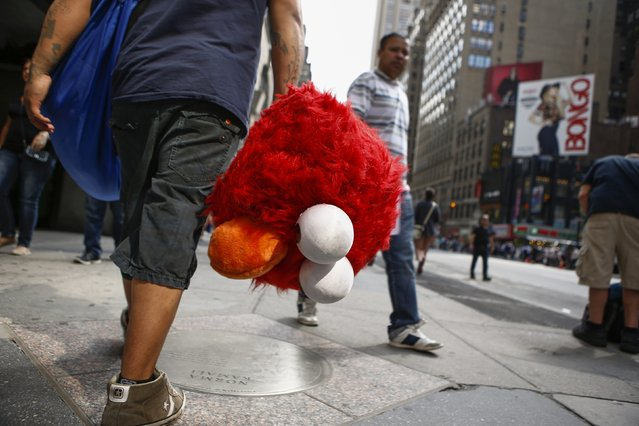 Jorge, an immigrant from Mexico, carries the head of the Sesame Street character Elmo while he walks through Times Square, New York July 30, 2014. (Photo by Eduardo Munoz/Reuters)