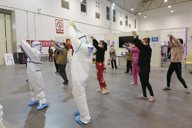 In this February 18, 2020, photo released by Zhang Junjian, medical workers lead patients in exercises at the Wuhan Living Room Temporary hospital in Wuhan in central China's Hubei province. The hospital is the largest of 16 temporary hospitals set up in gyms and other locations to handle an overflow of patients and try to stem the spread of the coronavirus by separating them from the rest of the city's 11-million inhabitants. (Photo by Zhang Junjian via AP Photo)