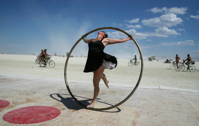 Burning Man participant Kylie Webb spins inside a metal hoop on a roller disco floor as approximately 70,000 people from all over the world gathered for the 1st full day of the annual Burning Man arts and music festival in the middle of the Black Rock Desert of Nevada, U.S. August 28, 2017. (Photo by Jim Urquhart/Reuters)